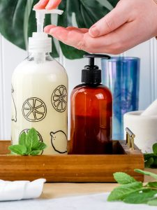 hand soap in a clear glass jar in a wooden tray next to other bottles on the bathroom countertop. a pair of caucasian hands are reading into the photo to use the soap