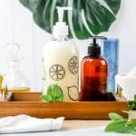 homemade hypoallergenic hand soap in a clear glass bottle is next to other bathroom bottles with a white towel and fresh mint leaves scattered around
