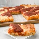 close up of detroit style pizza gluten free crust slice on plate with pizza behind it on the table