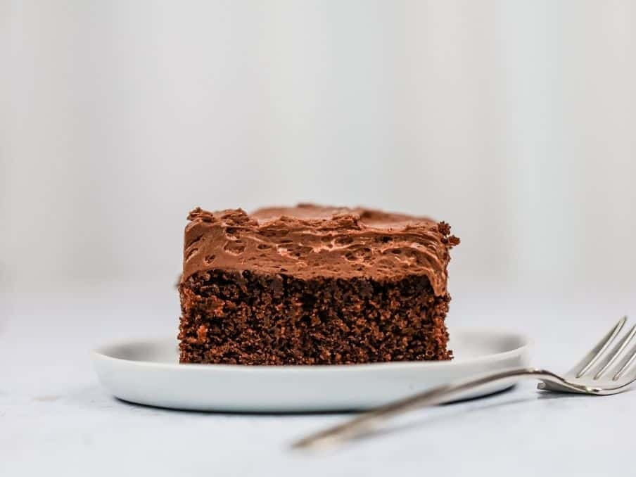 a slice of gluten free chocolate sheet cake rests on a small round white plate with a fork beside it