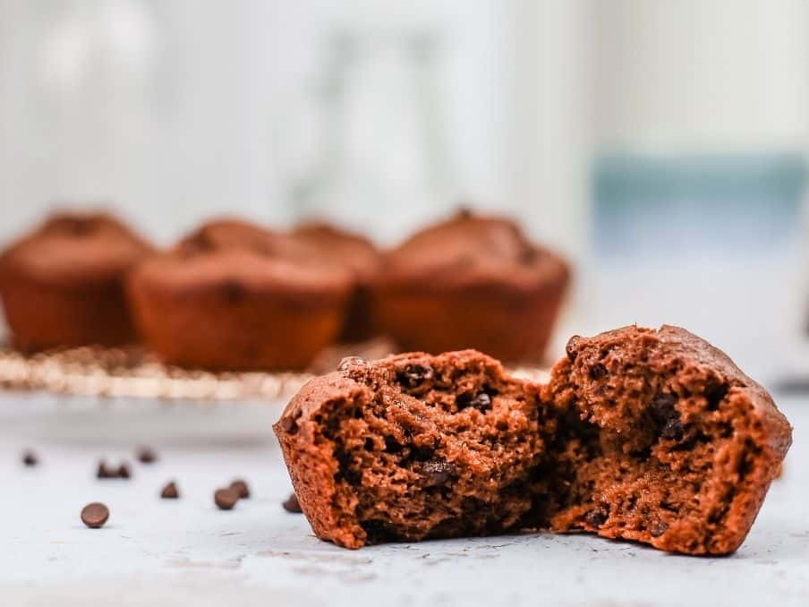 close up of gluten free vegan double chocolate muffins with one muffin in the foreground opened so you can see the delicious texture inside with more muffins in the background